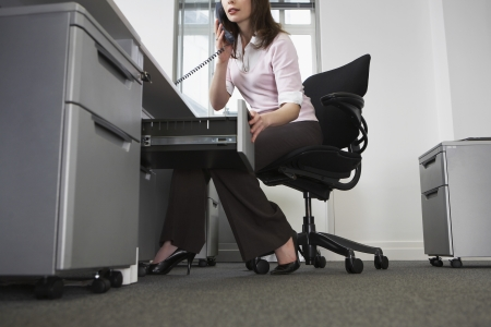 Woman sitting behind desk in office using phone and opening drawer Stock Photo - 19079167