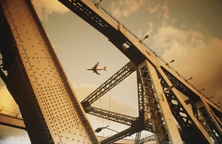 superstructure: Airbourne passenger jet viewed through bridge superstructure