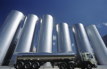 Milk transport truck parked alongside storage tanks Stock Photo - 20658997