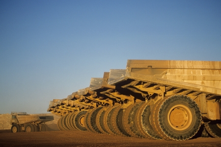 Ore hauling trucks in row Telfer Western Australia Stock Photo