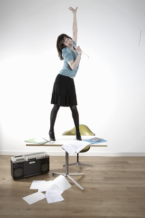 wasting away: Woman standing on desk and singing LANG_EVOIMAGES