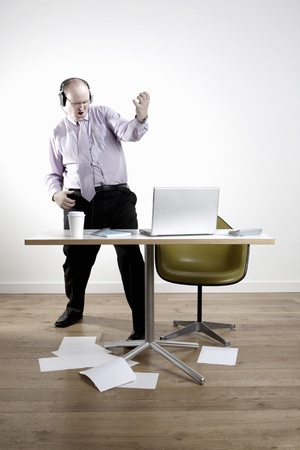 wasting away: Businessman with earphones fooling around at desk LANG_EVOIMAGES
