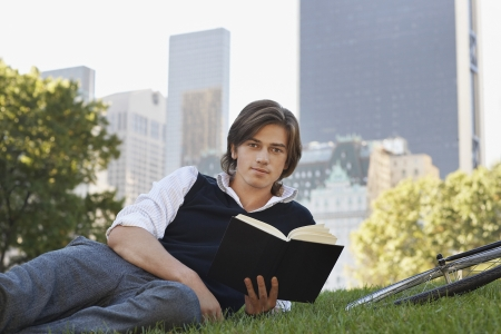 rolled up sleeves: Man lying on lawn holding book portrait