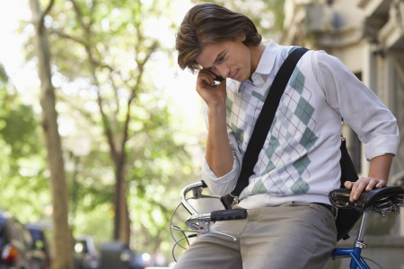 rolled up sleeves: Man sitting on bicycle talking on mobile phone LANG_EVOIMAGES