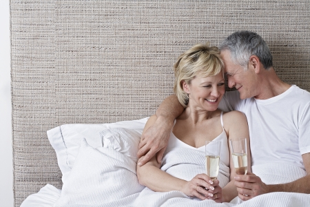 glass bed: Middle-aged couple drinking champagne in bed LANG_EVOIMAGES