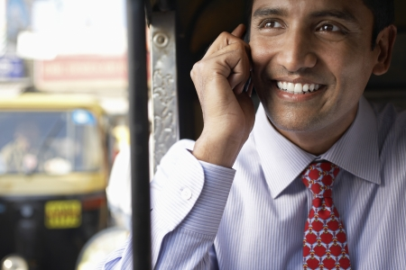indian business man: Business man using cell phone smiling LANG_EVOIMAGES