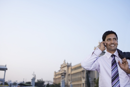 one person with others: Business man using cell phone smiling LANG_EVOIMAGES