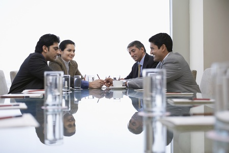 asian business people: Small corporate business meeting viewed along reflective surface of conference table