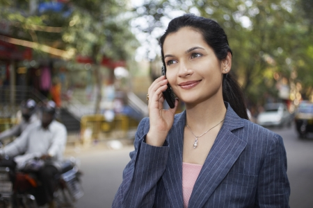 business woman phone: India business woman using mobile phone on street