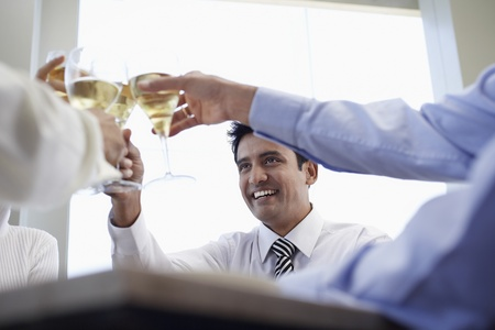 one person with others: Business associates toasting with wine glasses close-up