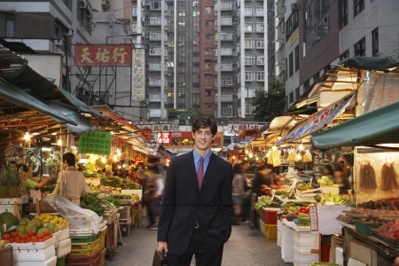 one person with others: Portrait of young business man at street market