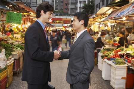 two people with others: Two business men shaking hands at street market
