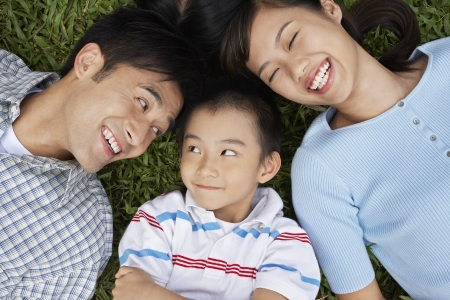 family life: Couple with son (7-9) lying on grass portrait elevated view