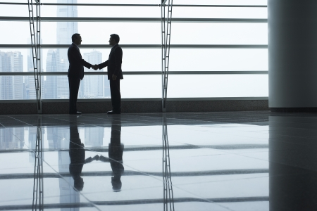 Handshake business: Silhouettes of two business men shaking hands