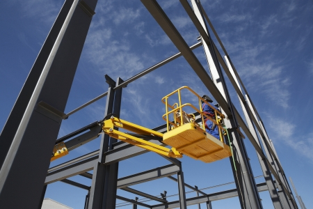 unknown age: Welder working from cherry picker on warehouse construction