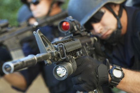 military watch: Swat officer aiming guns LANG_EVOIMAGES
