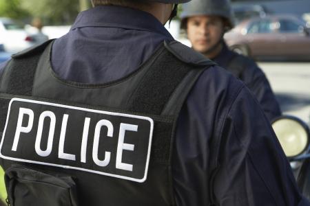 policier: L'officier de police dans le gilet pare-balles � l'ext�rieur vue arri�re