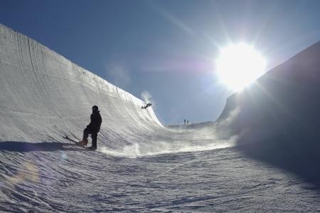 halfpipe: Silhouette of teenage snowboarder on halfpipe