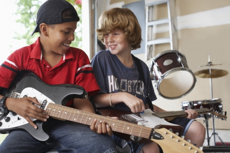 preteen boy: Two boys (10-12) with instruments in garage