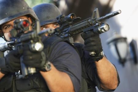 police helmet: Swat officers aiming guns LANG_EVOIMAGES