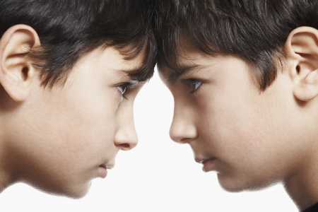 sibling rivalry: Twin boys (13-15) head to head close-up