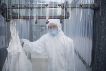 protective mask: Worker in protective mask and suit behind plastic wall