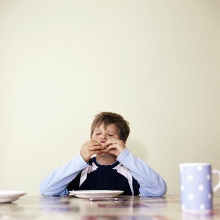 bad manners: Boy (7-9) eating at table with eyes closed