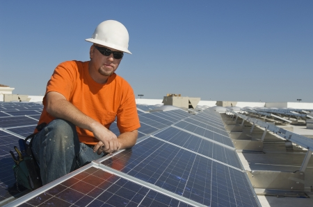 35 to 40 year olds: Electrical Engineer Among Solar Panels at Solar Power Plant