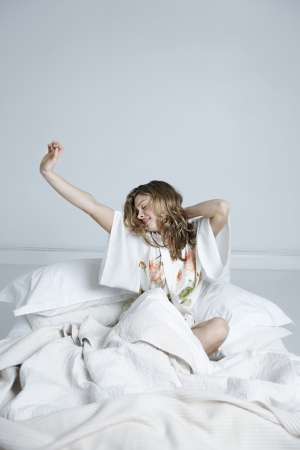 pattern bed: Young woman in dressing gown stretching in bed