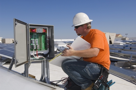 35 to 40 year olds: Engineer Working on Electrical Box at Solar Power Plant