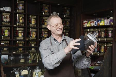 early fifties: Tea Shop Owner Dusting Jar of Tea LANG_EVOIMAGES
