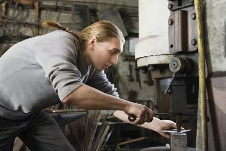 blacksmith shop: Blacksmith Using Press in Shop