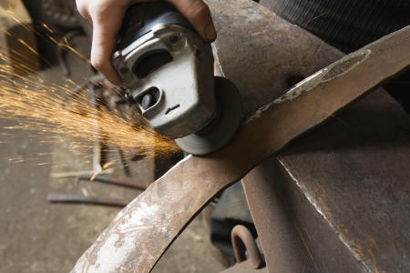 30 to 35 year olds: Blacksmith Grinding Edge of Metal Tool LANG_EVOIMAGES