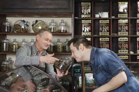 salespeople: Tea Shop Owner Showing Tea to Customer LANG_EVOIMAGES