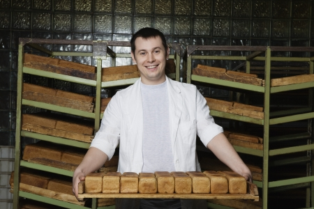 boulangerie: Baker Carrying Loaves of Fresh Bread LANG_EVOIMAGES