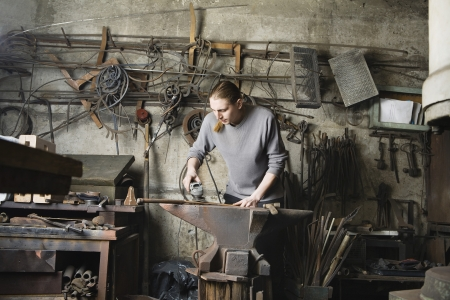30 to 35 year olds: Blacksmith Working in Shop