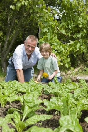 self sufficient: Boy gardening with grandfather portrait