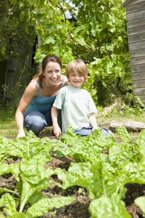 self sufficient: Boy gardening with mother portrait