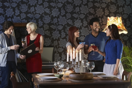 dinner party people: Group of people smiling standing by dining table