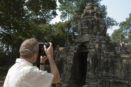 angkor wat: Man Photographing Ancient Temple LANG_EVOIMAGES
