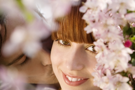 Young Man Kissing Woman Under a Blossoming Tree Stock Photo