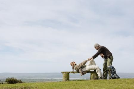 helpfulness: Man Helping Girlfriend up from a Park Bench