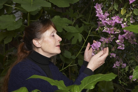 50 to 55 years old: Woman Examining Flowers