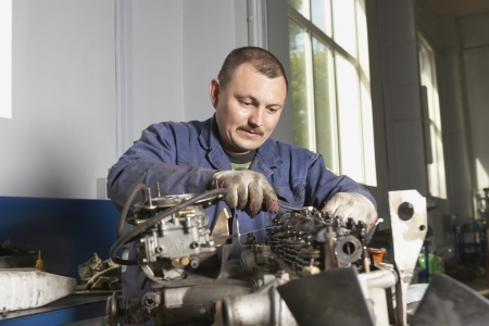 30 to 35 year olds: Mechanic Working on Motor
