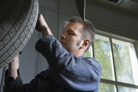 20 25 years old: Mechanic Working on Tire