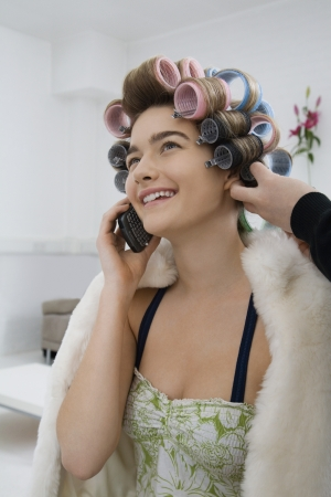 one person with others: Model on Cell Phone While Having Hair Curled LANG_EVOIMAGES