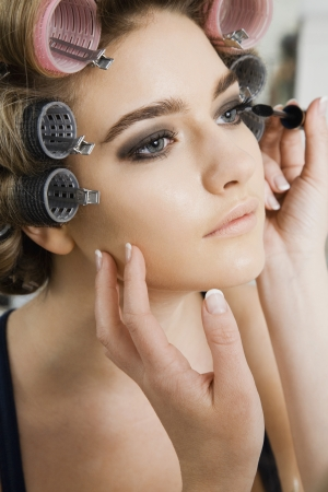 20 25 years old: Model in Hair Curlers Having Makeup Applied
