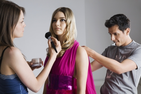 20 to 25 year olds: Designer and Makeup Artist Preparing Model for Photo Shoot