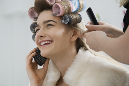 20 25 years old: Model on Cell Phone While Having Hair Curled LANG_EVOIMAGES