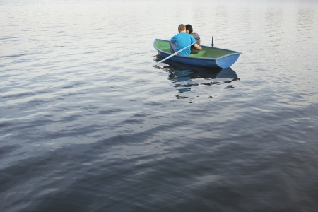 18 25 year old: Young Couple Cuddling in Rowboat on Lake